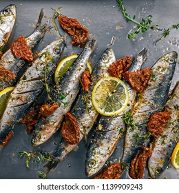 Raw sardine fish on a baking tray. Cooking of delicious seafood meal in an  oven. Directly above top view shot.