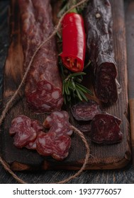 raw sausage with chili peppers and rosemary. on a wooden board and laces