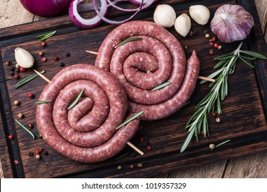 raw sausage on a wooden cutting board