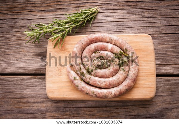 Raw sausage rolled on a wooden board with rosemary and thyme