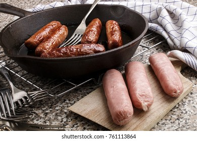 raw sausages on a wooden board and fried irish pork sausages in a cast iron pan