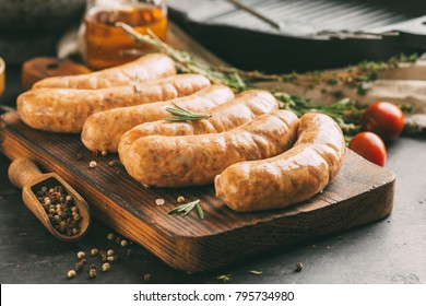 Raw sausages on a wooden cutting board with herbs and spices.