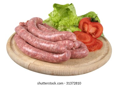 Raw sausages with vegetables on wooden cutting board