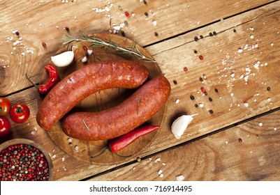 Raw sausages with vegetables and spices on wooden background