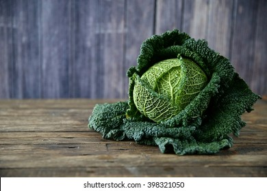 Raw savoy cabbage on wooden and grey background
