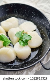 Raw scallops with herbs on frying pan