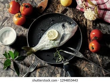 the raw sea bream on a cooking pan with some vegetables and spices