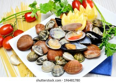 raw sea fruits called fasolari live again with lemon and spaghetti pasta ingredients