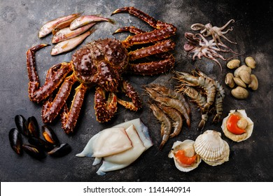 Raw Seafood - King Crab, Prawn Shrimp, Clams, Scallops, Octopus, Squid, Mullet fish on dark background