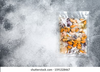 Raw seafood mix in vacuum packaging. Gray background. Top view. Space for text