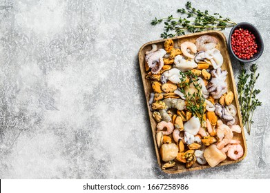 Raw seafood mix in a wooden bowl. Gray background. Top view. Space for text.