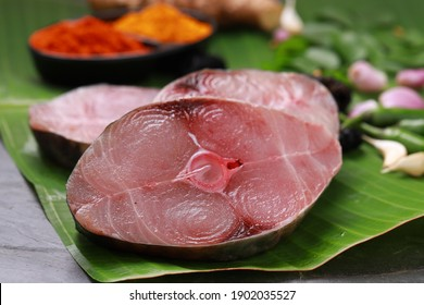 Raw Seer fish or Ayakura ,steaks of seer fish arranged on a fresh green banana leaf with cooking ingrediants on a grey textured background.