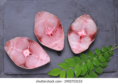 Raw Seer fish or Ayakura ,steaks of seer fish arranged on a graphite slate with grey colour background and garnished with fresh curry leaves ,isolated images.