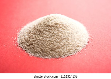 Raw Semolina flour or Rava powder is the coarse, purified wheat middlings of durum wheat. Served over plain background as a heap or in a bowl or spoon. Selective focus