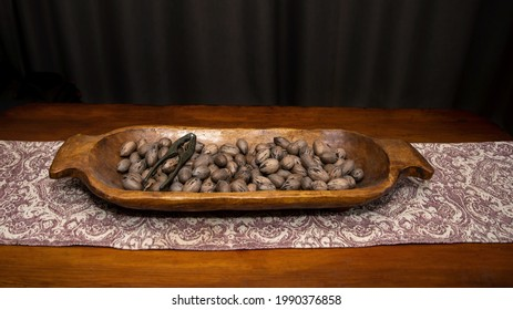 Raw in shell whole Pecan nuts in a wooden bowl on a wood table with a vintage nut cracker