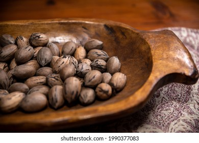 Raw in shell whole Pecan nuts in a wooden bowl on a wood table