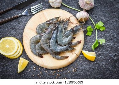 raw shrimps on wooden cutting board plate / fresh shrimp prawns for cooking with spices lemon on dark background in the seafood restaurant