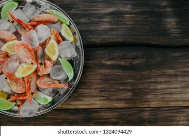 Raw shrimps plate with ice, lemon and lime slices on a wooden background. Top view, copy space