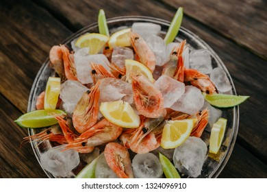 Raw shrimps plate with ice, lemon and lime slices on a wooden background.