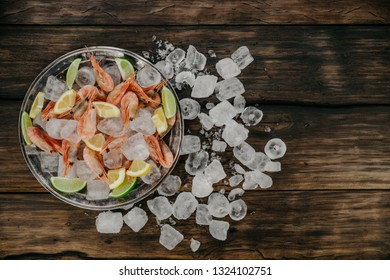 Raw shrimps plate with ice, lemon and lime slices on a wooden background.  Copy space, top view