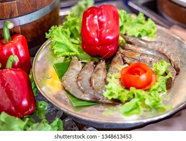 Raw shripms on silver plate decorate with flowered tomato and red paprika