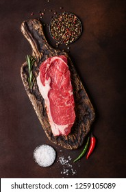 Raw sirloin beef steak on old chopping board with salt and pepper on rusty background.