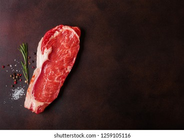 Raw sirloin beef steak on rusty background. Salt and pepper with fresh rosemary.