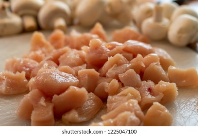 Raw sliced chicken pieces with mushrooms in the background.