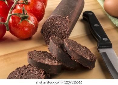 raw sliced irish black pudding on a wooden board
