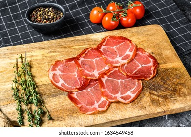 Raw smoked meat Jamon Lomo. Black background. Top view