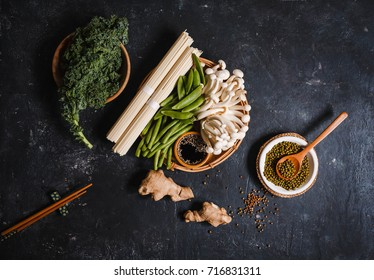 Raw somen noodles white beech mushroom and Ingredients for cooking asian food with greens vegetables spices on dark background