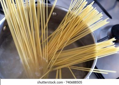 Raw spaghetti boiling in a silver pan
