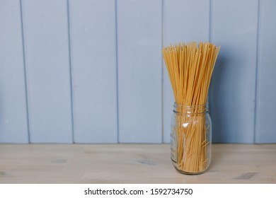 Raw spaghetti stand on the table in the kitchen in a glass transparent jar on a blue background