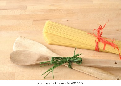 Raw spaghetti tied with a red ribbon on wooden table in the kitchen