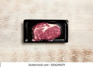 Raw steak in an airtight packaging