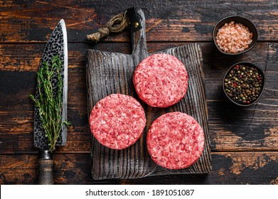 Raw steak burgers patties with ground beef and thyme on a wooden cutting board. Dark Wooden background. Top view.