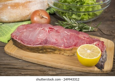 raw steak catfish on a cutting Board on the old wooden table