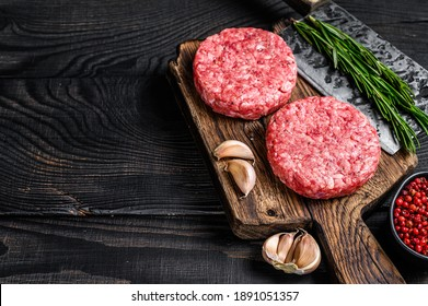 Raw steak cutlets with mince beef meat and rosemary on a wooden cutting board with meat cleaver. Black Wooden background. Top view. Copy space.