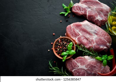 Raw steak. Meat with spices and herbs. On a black stone background. Top view. Free copy space.