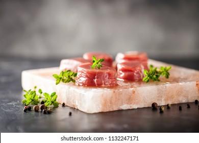 Raw Steak Ribeye on Himalayan pink salt block on dark  background