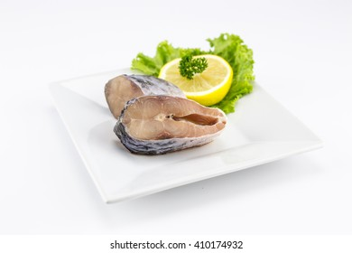 Raw steak of Rohu fish with lemon and lettuce. Isolate on white background