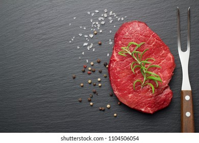 raw steak with salt and pepper on slate plate