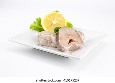 Raw steak of snake-head fish with lemon and lettuce. Isolate on white background