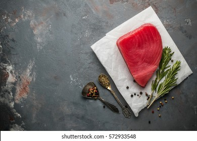 raw steak of tuna on the black plate around on the table the ingredients for cooking