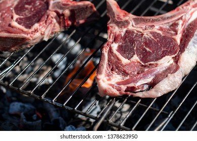 Raw steaks on a barbecue with flames.