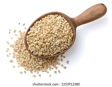 raw steel cut oats in the wooden spoon, isolated on the white background, top view