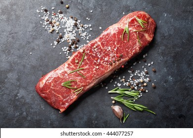 Raw striploin steak with rosemary, salt and pepper cooking over stone table