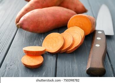 Raw sweet potato on wooden table