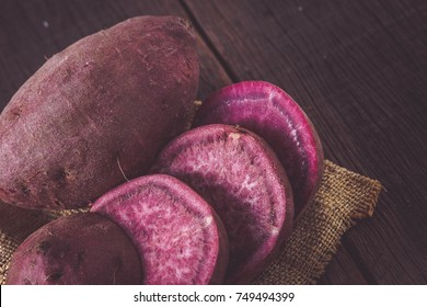 Raw sweet potatoes on wood background with filter effect retro vintage style