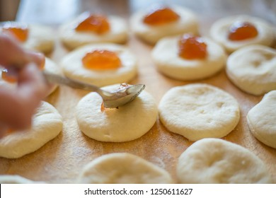 Raw sweet yeast dough on a wooden table, filling buns jam. Preparation for baking. The concept of chefs and baking.
